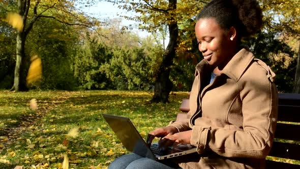 Cover Image for Young African Happy Girl Sits on Bench in Woods and Works on Laptop