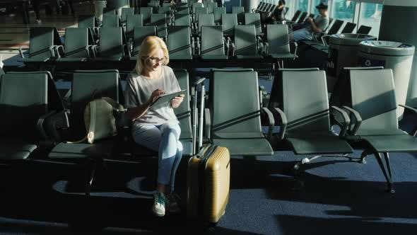 Young Woman Enjoys a Tablet in the Airport Lounge