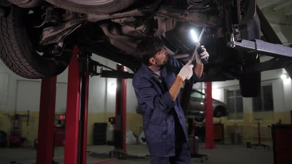 Thumbnail for Auto Mechanic Checking Chassis of Car on Lift