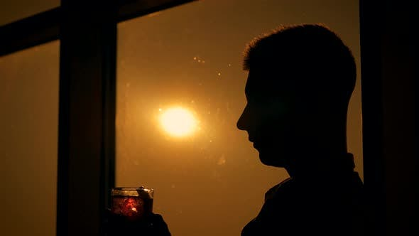 Thumbnail for A Man Drinks a Cocktail at Sunset. In the Background of the Window.