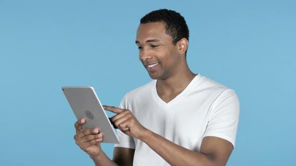 Thumbnail for African Man Browsing Internet, Using Tablet
