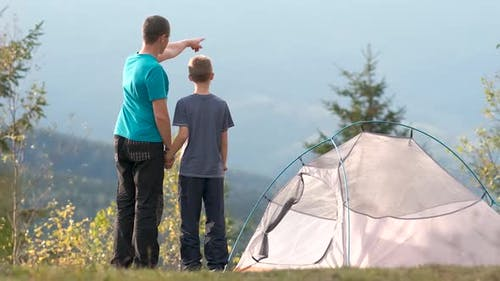 Father and his child son hiking together in summer mountains. Active family on camping trip.