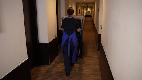 Cleaning Lady Driving Trolley Down Hotel Corridor
