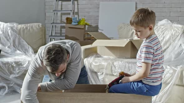Cover Image for Son Passing Electric Screwdriver to Father
