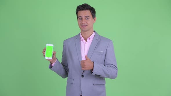 Thumbnail for Happy Young Handsome Businessman Showing Phone and Giving Thumbs Up