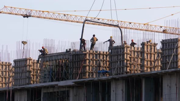 Thumbnail for Builders at a Construction Site. A Crane on a Construction Site Lifts a Load