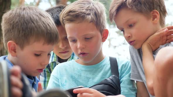 Thumbnail for Three Boys Playing Video Game. Three Brothers with Gadget. Faces of Three Boys with Phone Outdoor