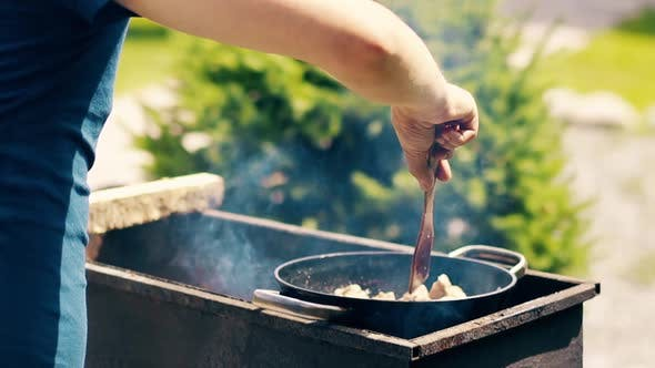 Thumbnail for Close-up, Slow Motion: Man Cooks Pilaf, in Cauldron, on Coals, on a Grill. Stir the Meat