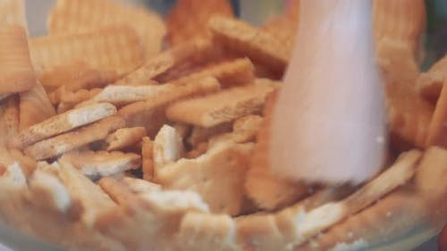 Cookies Are Crushed Into Crumbs in a Glass Bowl with a Pestle - Closeup