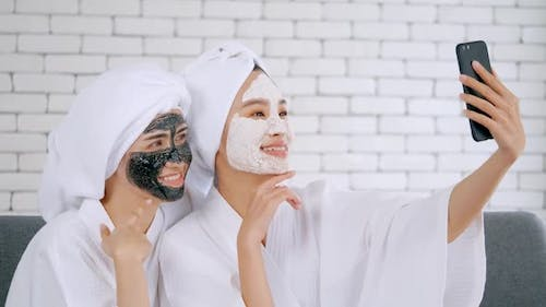Asian girls in white bathrobes with facial mask taking photo on smartphone together