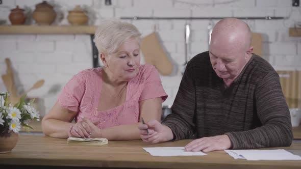 Thumbnail for Porträt von Senior Kaukasian Frau Blick auf ihren Mann Aufschreiben Budget. Paar Siedlung