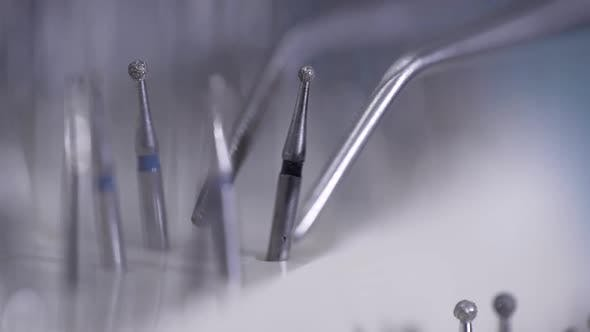 Stomatologist Is Taking Polishing Nozzle By Tweezers, Closeup in Medical Dental Office