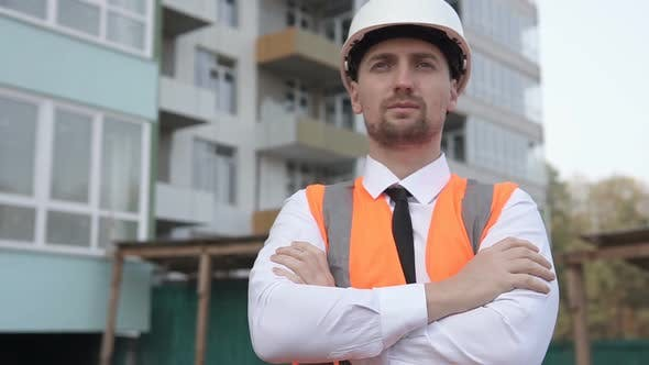 Engineer Builder Stands on a Construction Site with his Arms Crossed