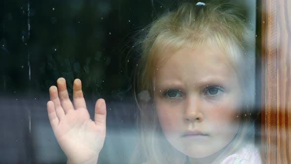 The girl is sad at the window