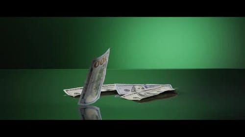 American $100 Bills Falling onto a Reflective Surface - MONEY 0038