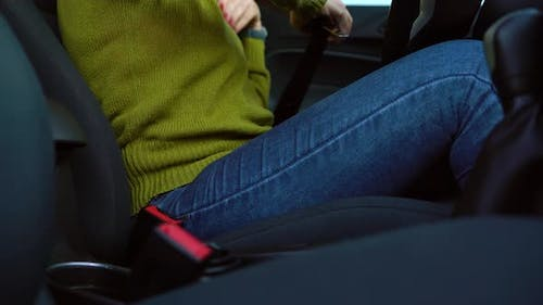 Female Hand Fastening Car Safety Seat Belt While Sitting Inside of Vehicle Before Driving