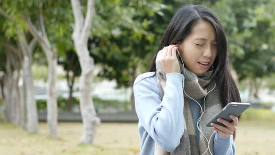 Thumbnail for Woman Listen to Music on Cellphone by Earphone