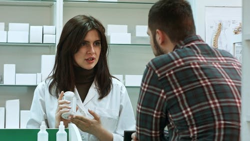 Young Female Pharmacist Suggesting Medical Drug to Male