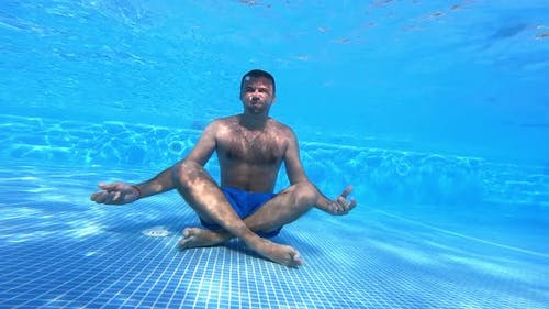 Man sits on the bottom of swimming pool. Healthy man is sitting in yoga pose underwater