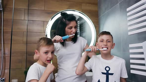 Thumbnail for Happy Mother and Her Sons Cleaning Together Their Teeth Using Brushes in the Bathroom