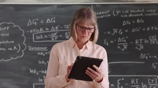 Independent senior woman teacher working on tablet device in front of chalkboard