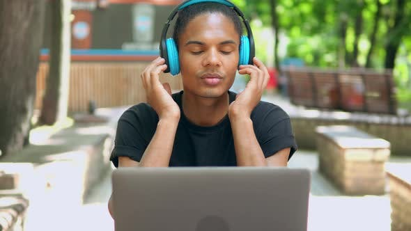 Cover Image for Front View Hipster Man Using Laptop and Headphones Outdoors
