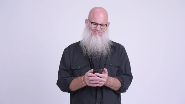 Thumbnail for Happy Mature Bald Bearded Man Smiling While Using Phone