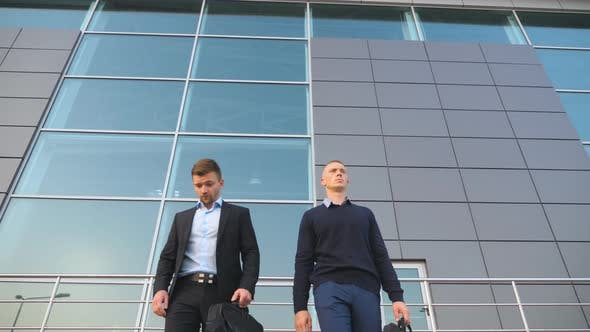 Thumbnail for Low Angle View of Two Young Successful Colleagues in Formal Wear Walking with Briefcases From Office