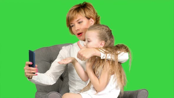 Happy Woman and Child Taking a Selfie on a Green Screen, Chroma Key