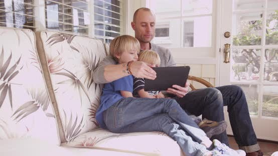 Thumbnail for Caucasian father and two children sitting looking at tablet computer