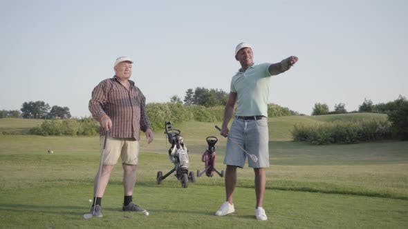 Thumbnail for Mature Caucasian Man and Young Middle Eastern Man Playing Golf on the Golf Course