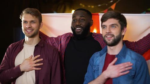 Caucasian and Black Male Friends Singing National Anthem, Waving English Flag