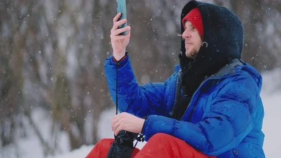 Cover Image for Male Snowboarder Sitting on the Snow Taking Photos on the Phone Beautiful Scenery