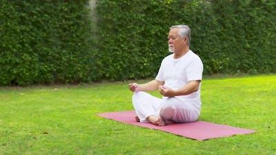 Asian Elderly man practicing meditating yoga.
