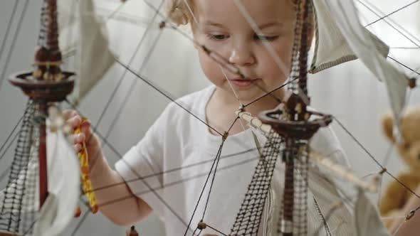 Thumbnail for Little Toddler  Boy Playing with Ship Model
