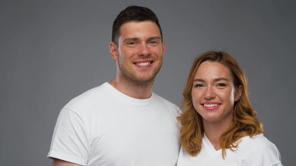 Couple in White T-shirts Over Grey Background