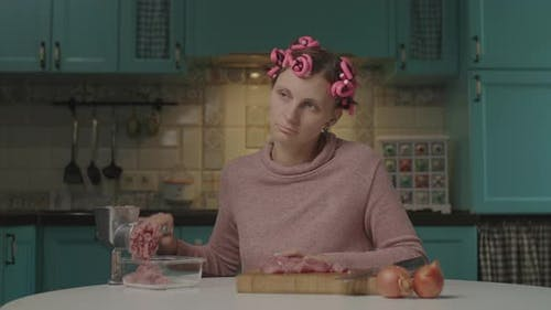 Tired 30s Young Woman with Hair Curlers on Head Mincing Meat in Mincer Sitting in the Kitchen