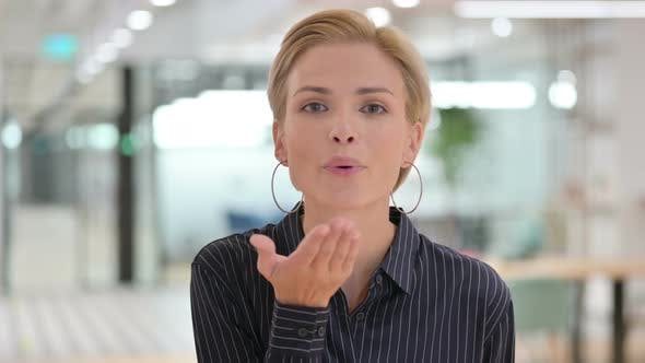 Beautiful Young Businesswoman Giving Flying Kiss