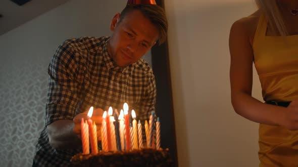 Thumbnail for Sexy Lady und hübscher Kerl leuchtet Kerzen auf leckeren Geburtstagskuchen. Prepearing für Party.
