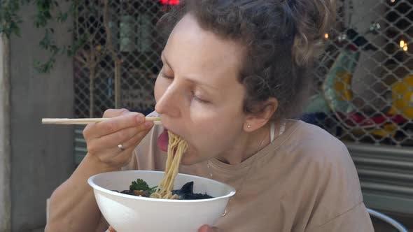 Healthy Vegan Asian Cuisine. Hungry Caucasian Girl Eating Vegan Ramen Soup with a Big Pleasure.