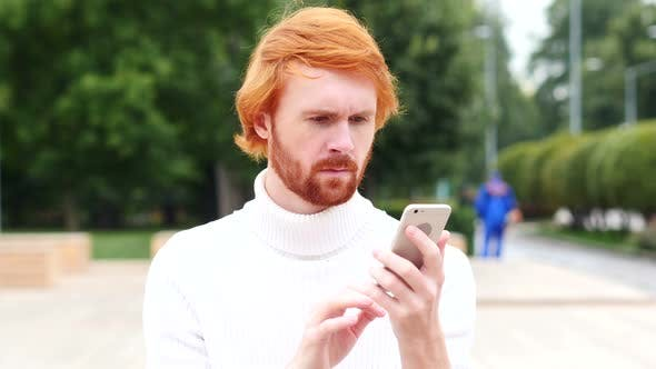 Thumbnail for Using Smartphone for Online Browsing, Man with Red Hairs, Outdoor