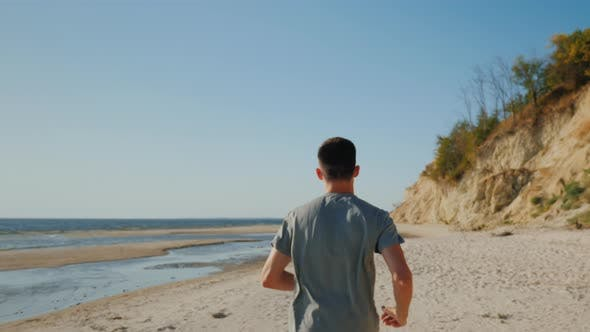 Cover Image for Young Man Jogging on the Beach in a Picturesque Place