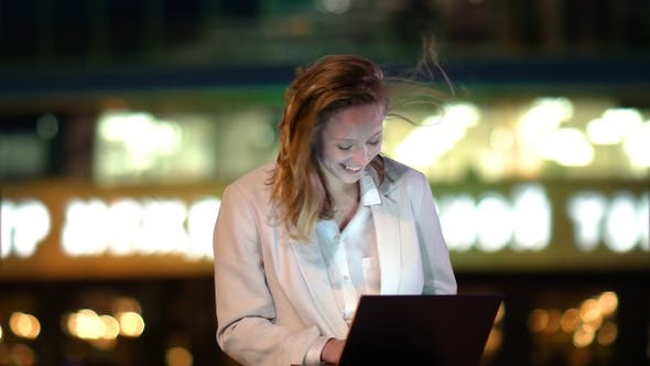 Thumbnail for Charming girl freelancer sitting on bench outdoors at night