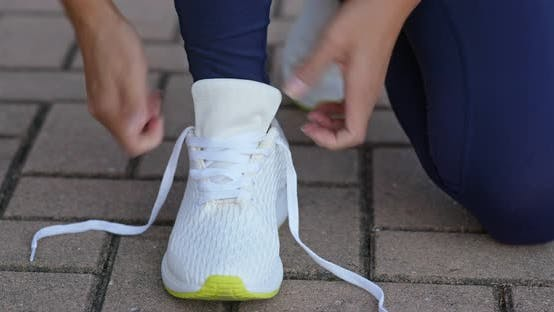 Thumbnail for Young adult female tying shoe lace before a run