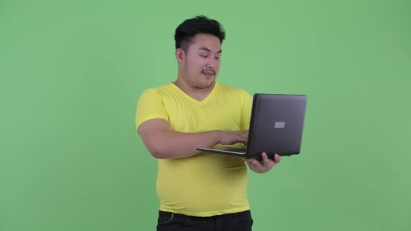 Thumbnail for Happy Young Overweight Asian Man Using and Showing Laptop