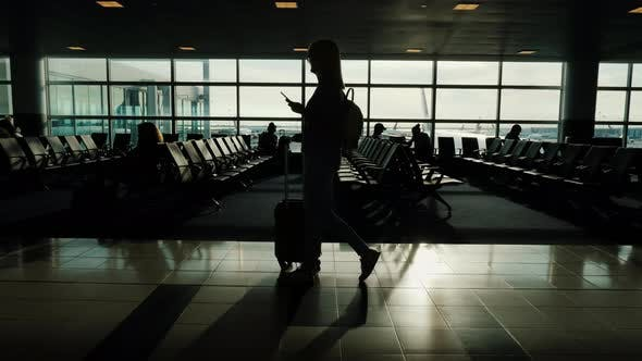 A Woman Is Walking Along the Terminal of the Airport, Carrying a Bag on Wheels. In the Hand