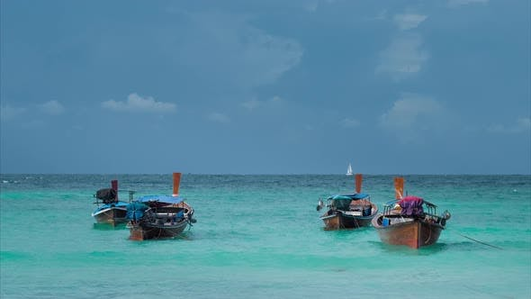Thumbnail for Four Long-tailed Boat Swinging in Blue Waves, White Sail Boat on the Horizon, Koh Lipe Thailand