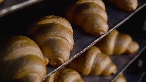 Nahaufnahme von Tellern mit gebackenen Croissants in einer Bäckerei