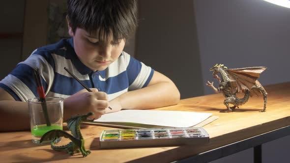 Ein Junge zeichnet Aquarell am Tisch sitzt, auf dem Spielzeug-Drachen stehen
