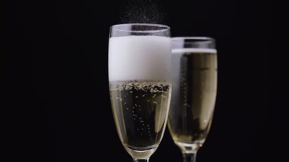 Thumbnail for Champagner in Glas gegossen. Schwarzer Hintergrund. Nahaufnahme